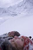 Two young woman lying on snow, Kuehtai, Tyrol, Austria