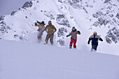 Four persons running downhill on snowcovered mountain, Kuehtai, Tyrol, Austria