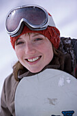 Laughing young woman with snowboard, Kuehtai, Tyrol, Austria