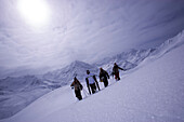 Four people with skies and snowboard walking up a snowcapped mountain, Kuehtai, Tyrol, Austria