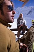 Couple sunbathing on terrace of ski lodge, Kuehtai, Tyrol, Austria