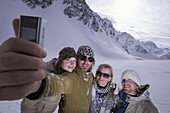 Four young skier taking a picture of themselves with a camera phone, Kuehtai, Tyrol, Austria