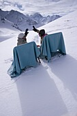 Two young people relaxing on lounge chairs on snow, Kuehtai, Tyrol, Austria