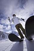 Young man with skis standing on snowcovered mountain, Kuehtai, Tyrol, Austria