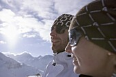 Young couple standing on slope, wearing sunglasses, Kuehtai, Tyrol, Austria