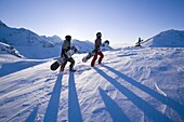 Two people carrying snowboards on slope, one person standing in background, Kuehtai, Tyrol, Austria