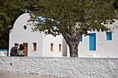 Couple sitting on the wall of Agios Ioannis Thymianos, a deserted monastery near Kefalos, Kos, Greece
