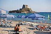 Couple at Kefalos beach kissing, Kastri island with capel St. Nicholas in background, Kefalos, Kos, Greece