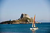 Catamaran in front of Kastri island with capel St. Nicholas, bay of Kefalos, Kefalos, Kos, Greece