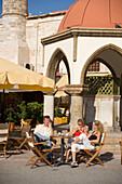 Three guests sitting in a pavement cafe near Defterdar-Mosque at Platia Eleftherias, Kos-Town, Kos, Greece