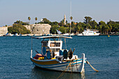 View over a fishing boat to Neratzia Castle, a former fortress of the Knights of St. John of Jerusalem, at Mandraki harbour, Kos-Town, Kos, Greece
