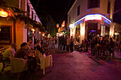 View inside a busy bar street with a lof of cafes and bars at night, Kos-Town, Kos, Greece