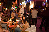 Waiter serving drinks in an open-air bar at night, Kos-Town, Kos, Greece