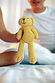 Child's hand holding teddy, close up