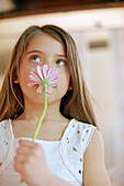 Girl taking a smell at a gerbera