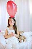 Mädchen spielt mit roten Luftballon