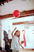 Girl dancing with red ball0ons