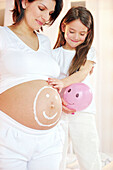 Pregnant woman with happy face on stomach