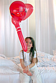 Girl holding red ballons