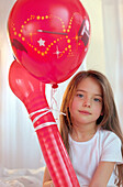 Girl holding red balloons, portrait