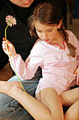 Girl sitting on fathers lap, holding flower in her hand