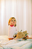 Toddler girl sitting with teddy on bed, Portrait
