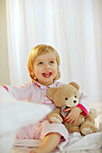 Toddler girl holding her teddy in bedroom