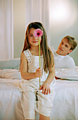 Girl with Gerbera on bed with father, portrait