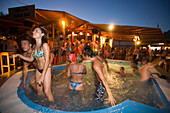Young people dancing in a pool during the full moon party of the Tropicana Club, Paradise Beach, Mykonos, Greece