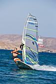 Surfer in action at Kalafati Beach, Kalafati, Mykonos, Greece