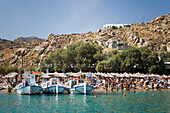Boats at bank of the peopled Super Paradise Beach, knowing as a centrum of gays and nudism, Psarou, Mykonos, Greece