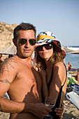 Man with sunglasses and tattoo embracing woman with a crazy hat and sunglasses at Super Paradise Beach, knowing as a centrum of gays and nudism, Psarou, Mykonos, Greece