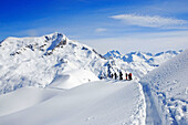 A group of skiers is standing in the remote deep snow ski area of Lech Zuers am Arlberg. Lech Zuers, Zürs, Arlberg, Austria, Alps, Europe.