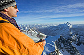 Man holding map looking over mountain panorama, Titlis summit, Urner Alps, Central Switzerland
