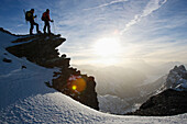 Two man standing on an exposed rock and admire the view from the Titlis. Titlis, view south west, Central Switzerland, Alps, Europe. MR