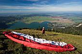 Paraglider on Jochberg, view over Lake Kochelsee, Upper Bavaria, Germany