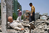demolition, doll, redevelopment area, migrant construction worker clearing bricks, Living amongst ruins, encroaching new highrise