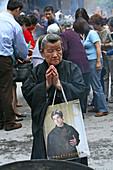 Longhua Temple,Longhua Temple and pagoda, oldest and largest buddhist temple in Shanghai, old lady with fashionable shopping bag, prayer
