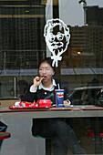 Fastfood restaurant window, woman eating American fastfood, KFC, Pepsi