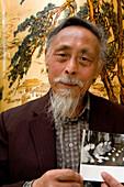 """Übersetzer Zhou Chun,translator Prof. Zhou Chun, shows an image of him with Chou En Lai, war einst Dolmetscher von Tschou En Lai und Mao Tse Tung, Großer Vorsitzender, dann politisch verfolgt, """"Rechtsabweichler"""", Gefängnis, kommunstischer Terror, Opfer, v"""