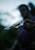 Hand holding a gun, group of people in background