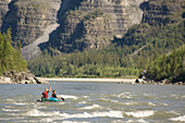 Two happy people in canoo after a difficult passage on South Nahanni River, Canada