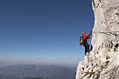 Young female climber at Donnerkogel fixed rope route, Gosaukamm, Dachstein Mountain, Austria