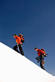 Two mountain climbers moving up a snowy mountain