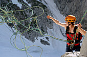 Female climber throwing rope during abseiling from Wilder Kaiser, Austria