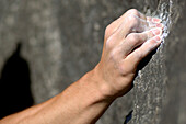 Climber's hand holding on rock face