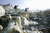 Young men walking on mountain path, near passo camerozzo,Sentiero  Roma, cengalo in back,  Bregaglia Mountains, Italy