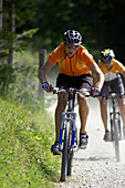 Two mountainbikers downhill on path with broken stones, Bavaria, Germany