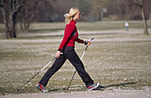 Nordic walking, young woman walking in a park, Munich, Germany