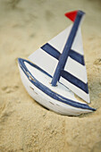 Wooden toy sailboat in the sand